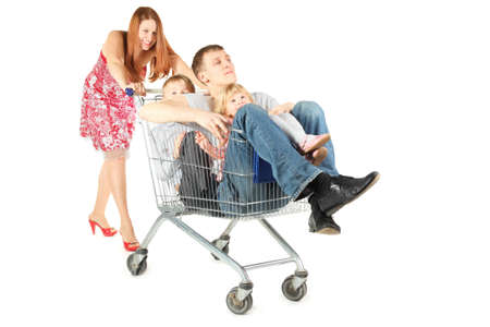 family with two children. father with son and daughter is sitting in shopping basket. woman is smiling. isolated. photo