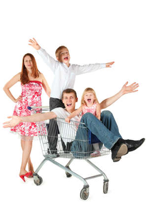 family with two children. joyful father with son and daughter is sitting in shopping basket. mother is standing behind shopping basket. isolated. photo