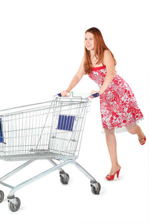 joyful woman wearing dress is moving shopping basket. isolated. photo