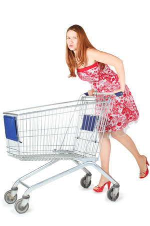attractive woman wearing dress is moving shopping basket. isolated. Stock Photo - 12130563