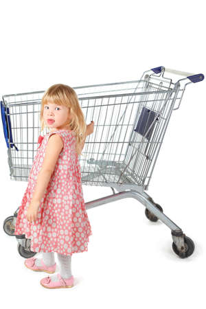 little girl wearing dress is standing near shopping basket. isolated. Stock Photo - 12130557