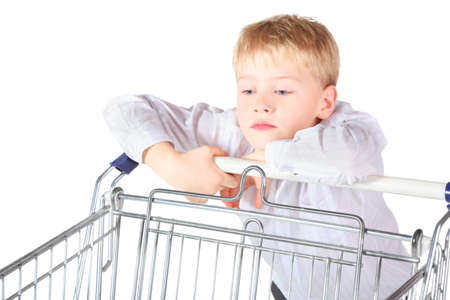 sadness boy is standing near shoping basket and looking in it. focus on boy's face. isolated. Stock Photo - 12130544