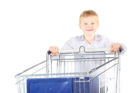 smiling boy is standing near shoping basket. focus on boy's face. isolated. Stock Photo - 12130408