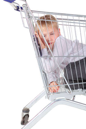 handsome little boy is trying to sleep in shoping basket. isolated. photo