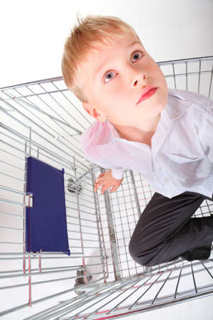 little boy is sitting in shoping basket and looking away. isolated. photo