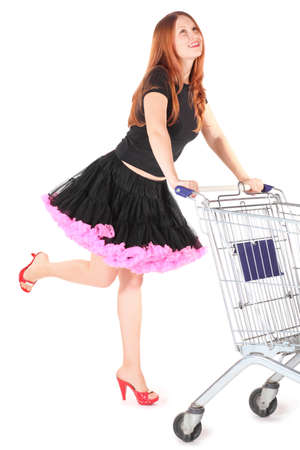 beautiful woman wearing dress is moving shoping basket and looking away. isolated. Stock Photo - 12130511