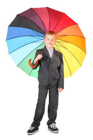 little boy wearing suit and sneakers is standing with rainbow colored umbrella. isolated. photo