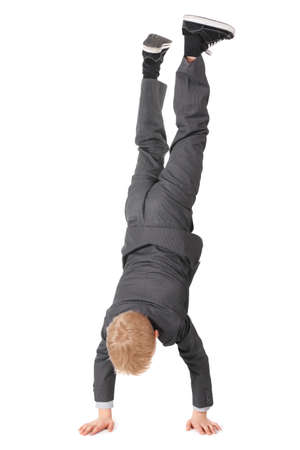 little boy wearing suit and sneakers doing handstand. isolated. photo