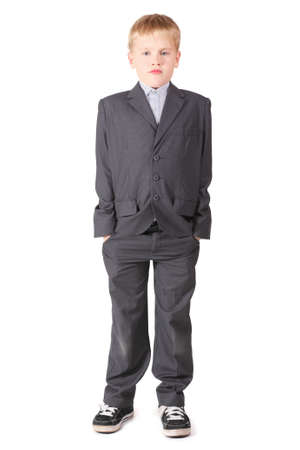 serious little boy is standing with hands in pockets. isolated. photo