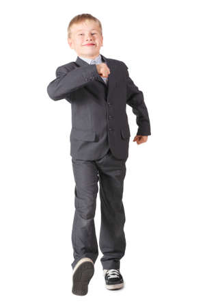 joyful schoolboy wearing a cute suit walking proudly. isolated. photo