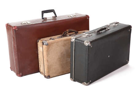 bight: three old dirty dusty suitcase. focus on front corner of yellow suitcase. isolated Stock Photo