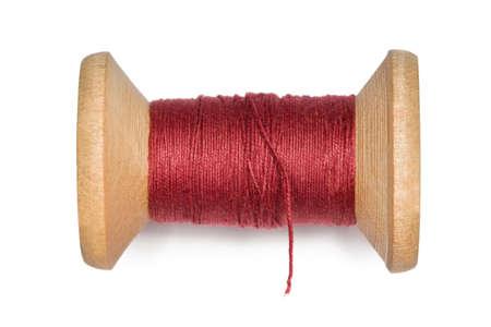 hilo rojo: bobina de madera con hilos rojos sobre fondo blanco Foto de archivo