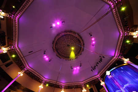 circus interior view on celling with pink light lamps and blue curtain