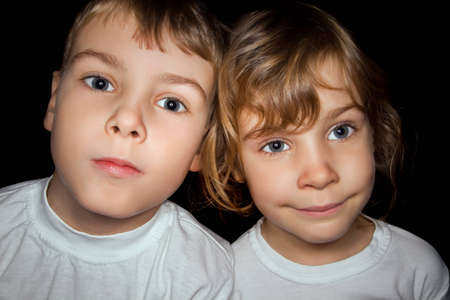 vicinity: boy and little girl in white T-shirts isolated on black background Stock Photo