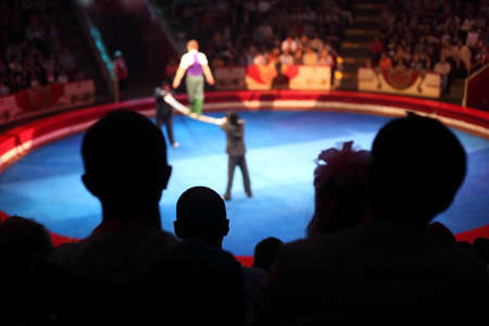 spectator: blue arena in circus performance with acrobat on bean focus on spectator