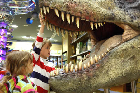 little boy and girl looking in tyrannosaurus opened mouth focus on boy side view