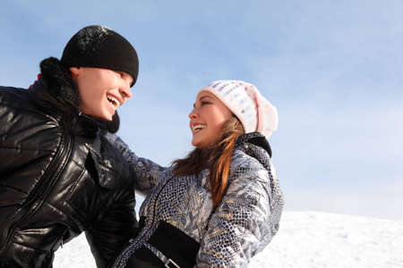 young man and girl embracing, smiling and looking to each other, winter day photo