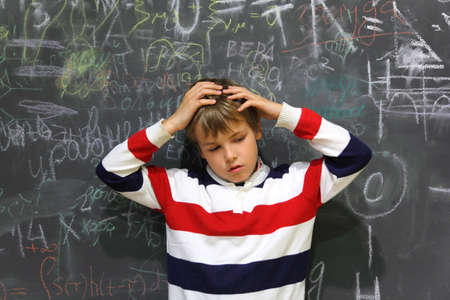 half body: pupil standing near school board and hold on his head half body sad face