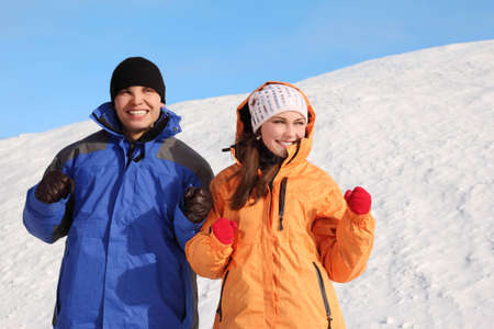 young man and girl in sport clothes dancing and smiling, half body, winter day photo