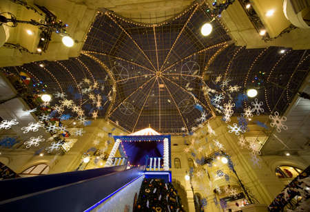 festoons: modern shopping center interior at night. Glass roof foreshortening from below. GUM, Moscow, Russia Editorial