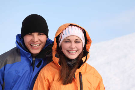 young man and girl in sport clothes standing and smiling, half body, winter day photo