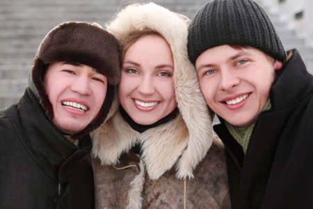three friends smiling and looking at camera, half body, winter day, stairs on background photo