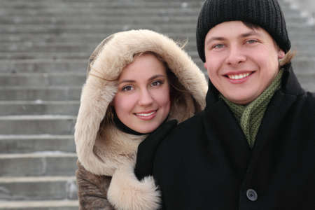 young girl in coat with hood embracing man from back and smiling, half body, winter day, stairs on background photo