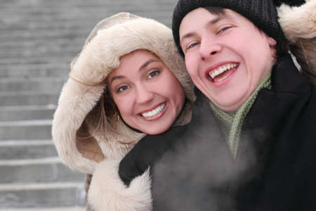 young girl in coat with hood embracing man from back and laughing, half body, winter day, stairs on background photo