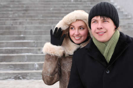 young girl in coat with hood and man in black dress smiling and looking left, half body photo