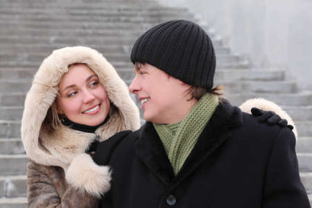 young girl in coat with hood and man in black dress smiling and looking to each other, half body photo