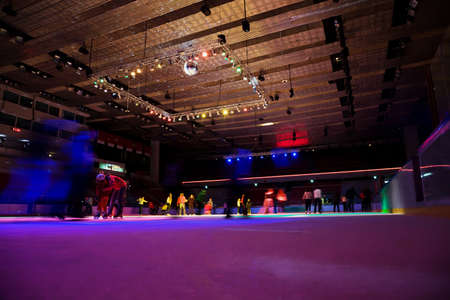 big covered skating rink with multi-coloured illumination in sports complex, on skating rink set of people, foreshortening from below