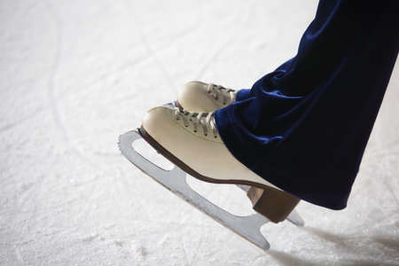 brink: Human feet in fads standing on ice on the brink of an edge on skating rink Stock Photo