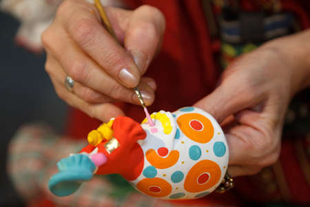 clay craft: Painting pottery figurines. Russian folk craft. Close-up photos.