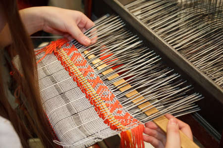 weft: Woman working at the loom. Russian national crafts. Focus on the fabric.