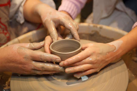 Hands of two people create pot on potter's wheel. Teaching traditional crafts. Focus on the hands.