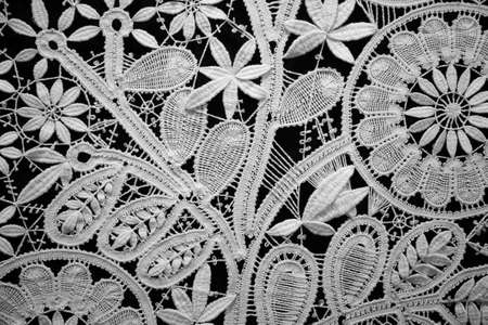 craft product: Lace doily on black background, close up. Horizontal format.