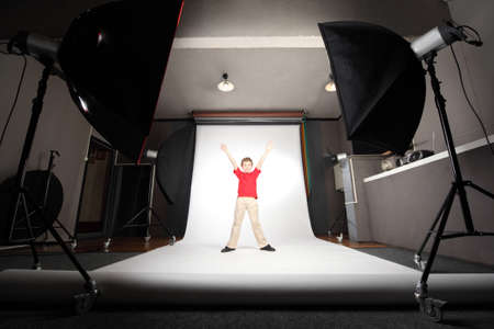 interior of professional photo studio boy in red shirt standing on white background photo