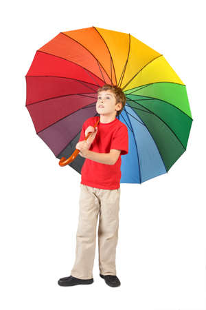 boy in red shirt with big multicolored umbrella standing on white and looking at side Stock Photo