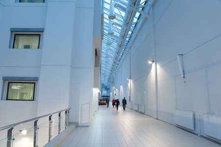 Long bright corridor through which people go. Office interior. Stock Photo - 12512064
