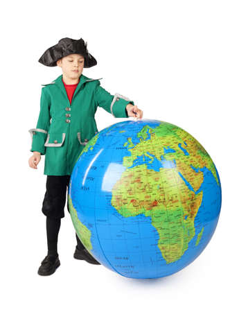 columb: little boy in historical dress standing with big inflatable globe isolated