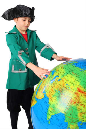 columb: little boy in historical dress looking at big inflatable globe isolated