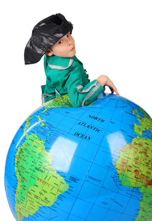 columb: boy in historical dress leans on inflatable globe isolated on white