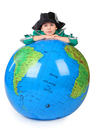 role models: boy in historical dress leans on inflatable globe chin on hands  isolated on white