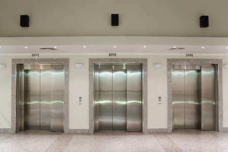 elevator: Three elevator doors in corridor of office building