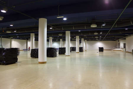 Large, empty warehouse. Ventilation and lighting equipment is mounted on ceiling.