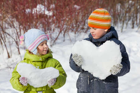 keeps:  teenager boy and little girl keeps in hands hearts from snow in winter in wood
