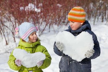 Teenager Junge und kleines Mädchen hält in den Händen Herzen von Schnee im Winter in Holz Standard-Bild - 12614140