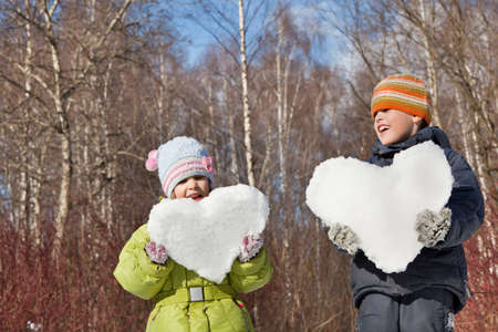 keeps: boy and little girl keeps in hands hearts from snow in winter in wood Stock Photo