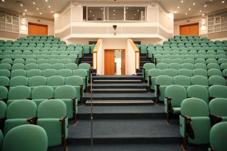 Interior of the hall for holding conferences. Rows of chairs for the audience and stage. Focus on the chairs.