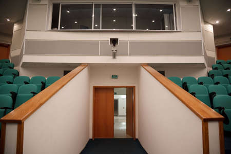 Interior of hall for conferences. Rows of chairs for spectators. View of the entrance to the hall.